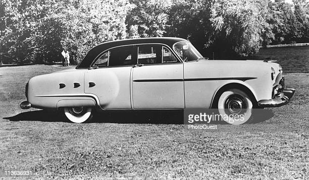 Promotional portrait of the Packard 200 Deluxe Touring sedan parked on grass, 1951.