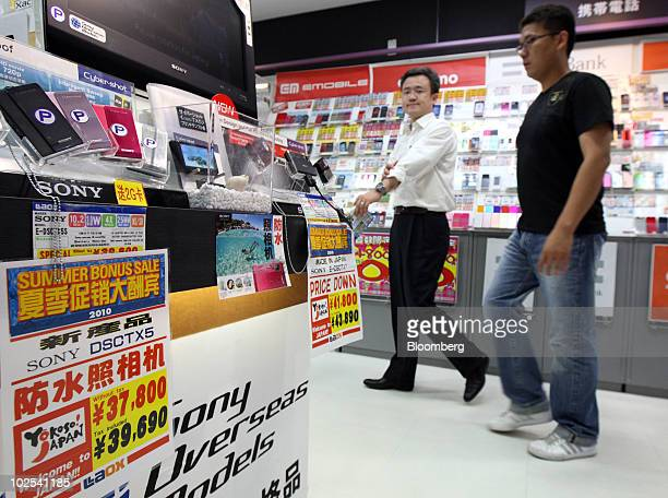 Promotional signs written in Chinese are displayed as tourists from China browse through a Laox Co shop in the Akihabara district of Tokyo Japan on...