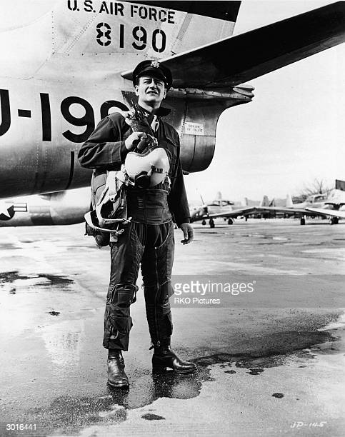Promotional still of American actor John Wayne standing on a runway in front of a plane in costume as a US Air Force pilot in a still from the film...