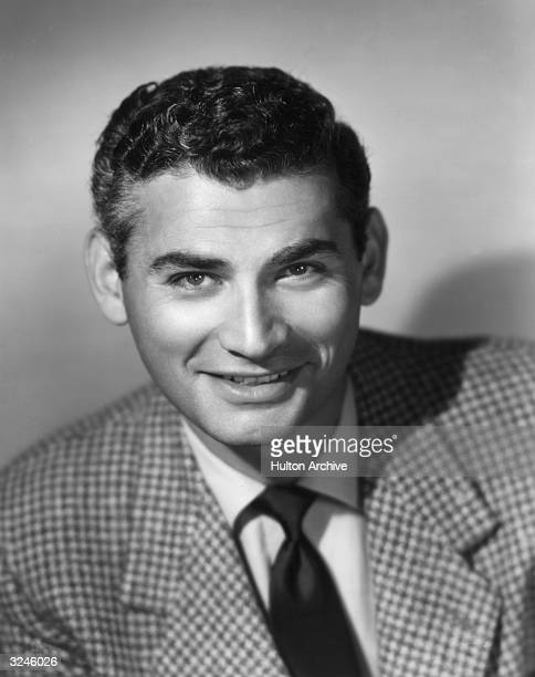 Promotional studio headshot portrait of American actor Jeff Chandler wearing a checked blazer and a dark tie..