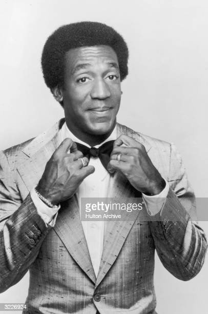 Promotional studio portrait of American actor and comedian Bill Cosby adjusting his bow tie from his television series 'The Bill Cosby Show'