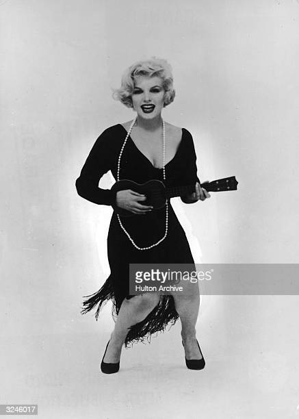 Promotional studio portrait of American actor Marilyn Monroe playing the ukulele for director Billy Wilder's film 'Some Like It Hot' She wears a...