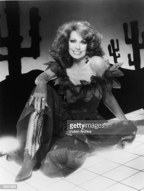 Promotional studio portrait of American country singer Dottie West wearing cowboy boots and seated on a Western desert backdrop circa 1979