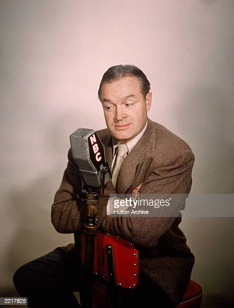Promotional studio portrait of British-born comedian and actor Bob Hope sitting at an NBC radio microphone, 1940s.