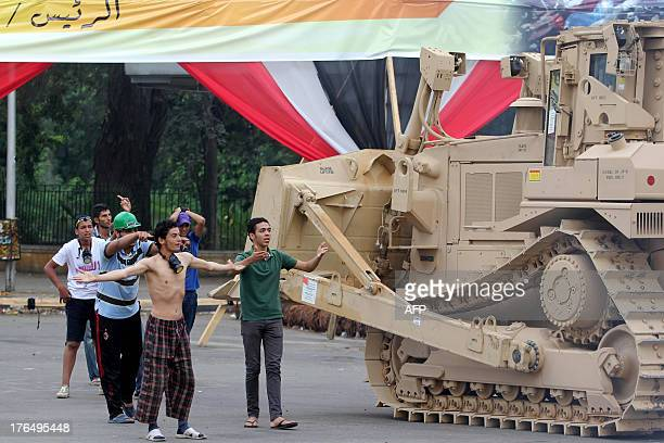 Pro-Muslim Brotherhood demonstrators react as an Egyptian military bulldozer dismantles Cairo's Al-Nahda square protest camp after Egyptian security...