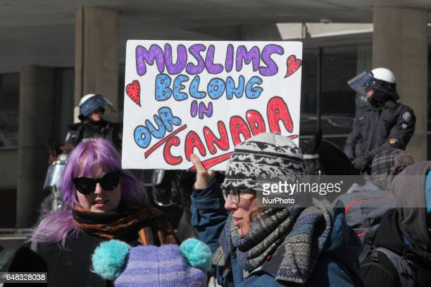 ProMuslim protestor carrying a sign saying 'Muslims Belong in Our Canada' as opposing groups of protesters clashed over the M103 motion to fight...