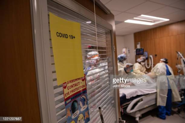 "Prone team,"" wearing personal protective equipment , prepares to turn a COVID-19 patient onto his stomach in a Stamford Hospital intensive care unit..."