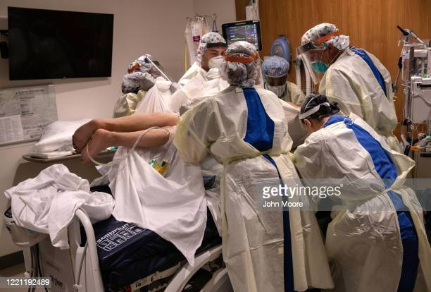 """Prone team,"""" wearing personal protective equipment , turns a COVID-19 patient onto his stomach in a Stamford Hospital intensive care unit , on April..."""