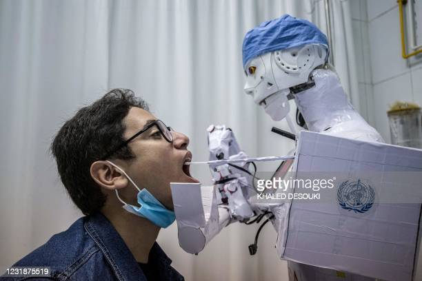 Prong extending from the CIRA-03 remote-controlled robot prototype approaches the mouth of a volunteer to extract a throat swab sample, as part of a...