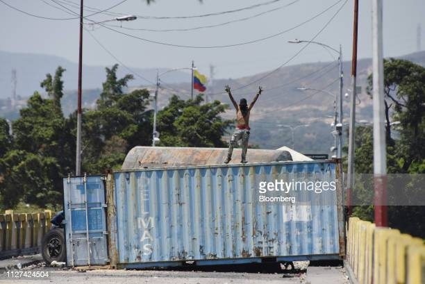 A proopposition demonstrator stands on top of a container set up as a barricade during a protest on the Simon Bolivar International Bridge in San...