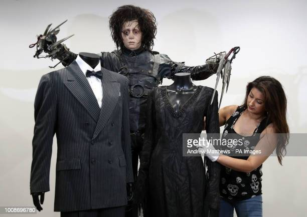 Prop Store employee adjusts the signature costume of Morticia Addams from the Addams Family on display alongside the signature costume of Gomez...