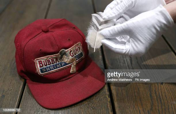 A Prop Store employee holds a feather from the film Forrest Gump estimate alongside a Bubba Gump cap worn by Tom Hanks in the Prop Store head office...