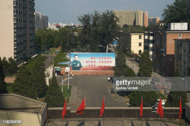 Propaganda billboard depicting Chinese President Xi Jinping is seen outside a military facility on July 15, 2019 in Beijing, China. The sign reads:...