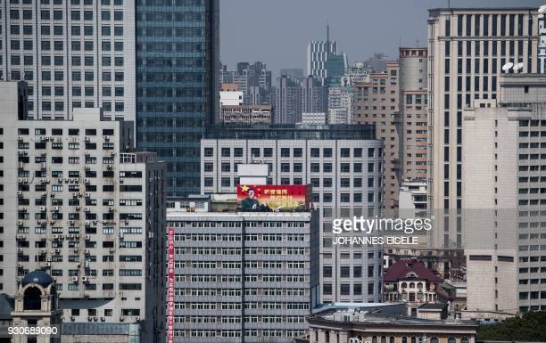 TOPSHOT A propaganda poster showing China's President Xi Jinping is pictured on a highrise building in downtown Shanghai on March 12 2018 China's Xi...