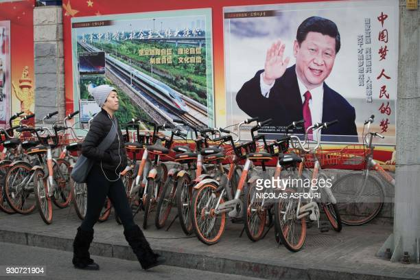 TOPSHOT A propaganda poster showing China's President Xi Jinping is pictured on a wall in Beijing on March 12 2018 China's Xi Jinping on March 11...