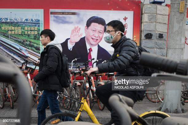 A propaganda poster showing China's President Xi Jinping is pictured on a wall in Beijing on March 12 2018 China's Xi Jinping on March 11 secured a...