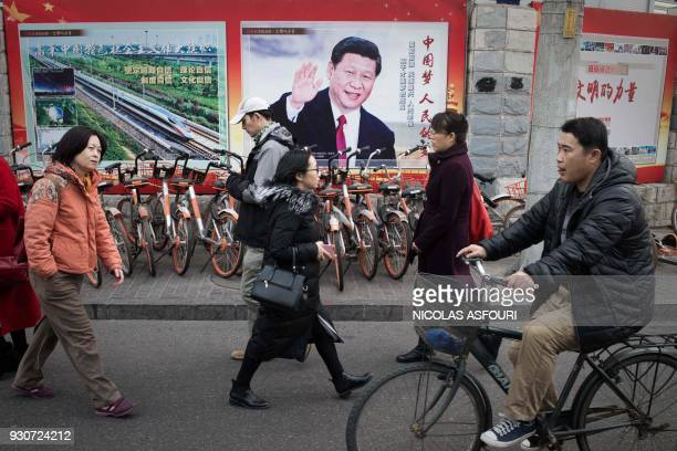 TOPSHOT A propaganda poster showing China's President Xi Jinping is pictured on a wall in Beijing on March 12 2018 Xi on March 11 secured a path to...