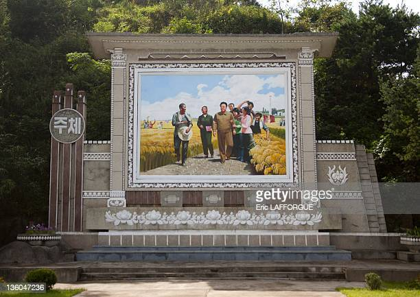 Propaganda poster with Kim Jong Il and farmers on September 12 2011 in Pyongyang North Korea