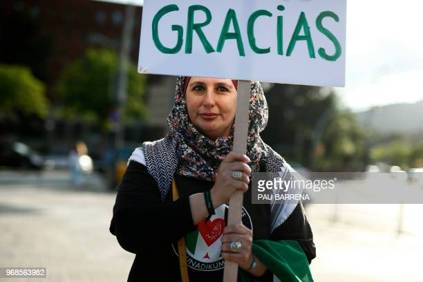 A proPalestine activist holds a placard reading 'Palestine says thanks' as they gather to celebrate the cancellation of a scheduled friendly football...