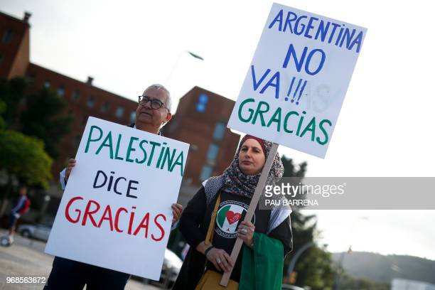 ProPalestine activists hold placards reading in Spanish 'Palestine says thanks' and 'Argentina doesn't go Thanks' as they gather to celebrate the...