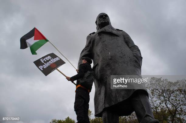 A proPalestine demonstrator waves Palestine flag and holds a placard on the statue of Sir Winston Churchill London on November 4 2017 The...