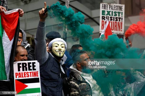 Pro-Palestinian activists and supporters let off smoke flares, wave flags and carry placards during a demonstration in support of the Palestinian...