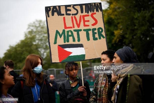 Pro-Palestinian activists and supporters wave flags and carry placards during a demonstration in support of the Palestinian cause as violence...