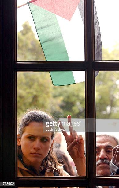 A proPalestinian demonstrator gestures through a window at a group of demonstrators that occupied the building April 9 2002 during a demonstration on...
