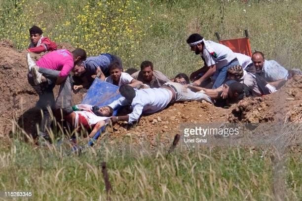 A proPalestinian demonstrator is helped after being shot at by Israeli troops in the Druze village of Majdal Shams on June 5 2011 in Israel Israeli...
