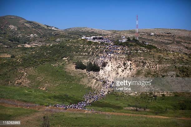 ProPalestinian demonstrators walk towards a ceasefire line as seen from the Druze village of Majdal Shams on June 5 2011 in Israel Israeli troops...