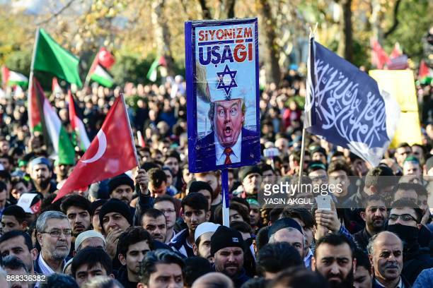 A proPalestinian protester holds a poster of US President Donald Trump reading 'servant of Zionism' during a demonstration in Istanbul on December 8...