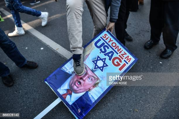 A proPalestinian protester steps on a poster of US President Donald Trump reading 'servant of Zionism' during a demonstration in Istanbul on December...