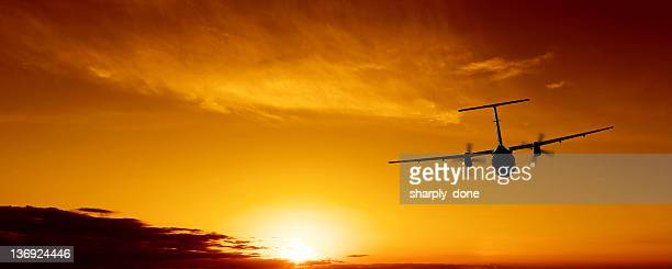 propeller airplane flying at sunset