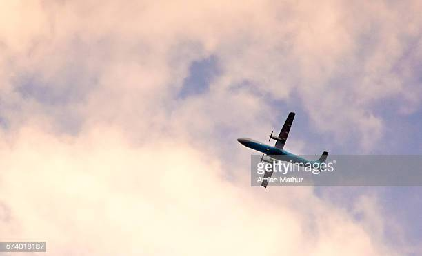 Propellor plane flying in pink clouds