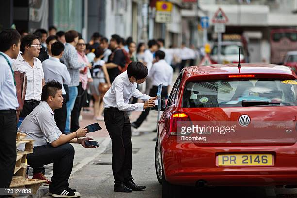 A property agent shows his business card and a brochure to a motorist outside the Bayview residential property developed by Kerry Properties Ltd in...