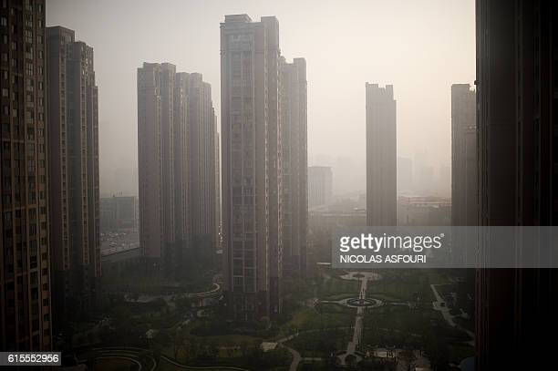 TOPSHOT Property buildings are seen surrounded by polution in Zhengzhou on October 19 2016 China's growth was steady at 67 percent in the third...