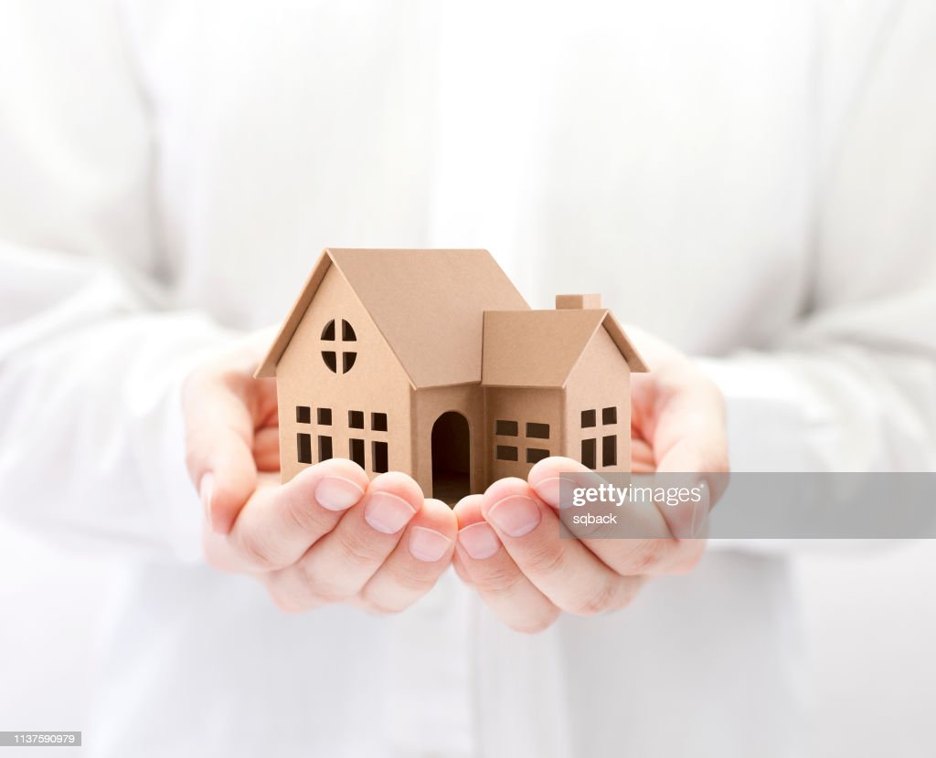 Property insurance. Cardboard house miniature in hands : Stock Photo