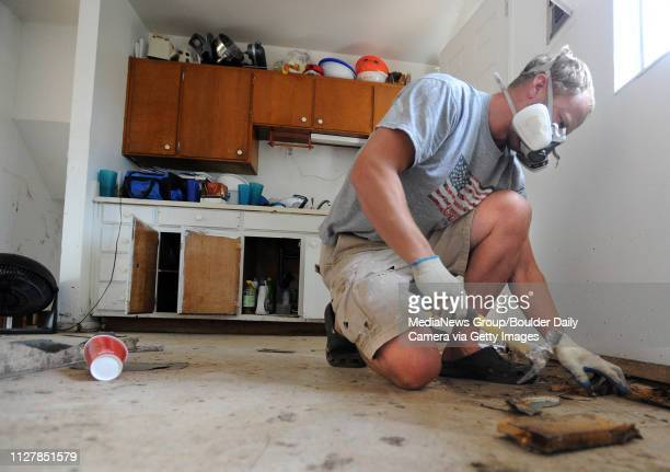 Property Manager Jamie McMaster removes a damaged kitchen floor at a home on Moorhead Ave in Boulder