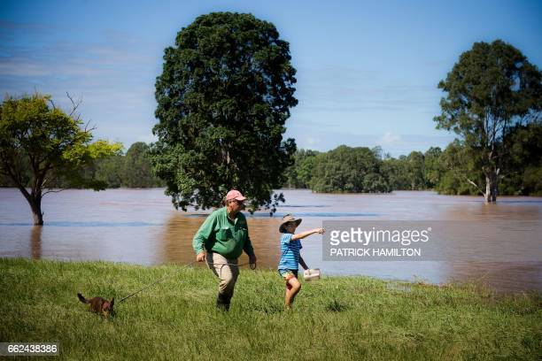 Property owner Tom Archibald walks with his son Blaze and dog Shadow on the flooded banks of the Logan River caused by Cyclone Debbie in North...