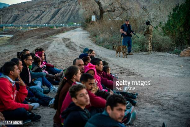 TOPSHOT Propery owner Jeff Allen stands near a group of about 30 Brazilian migrants who had just crossed the border at his property in Sunland Park...