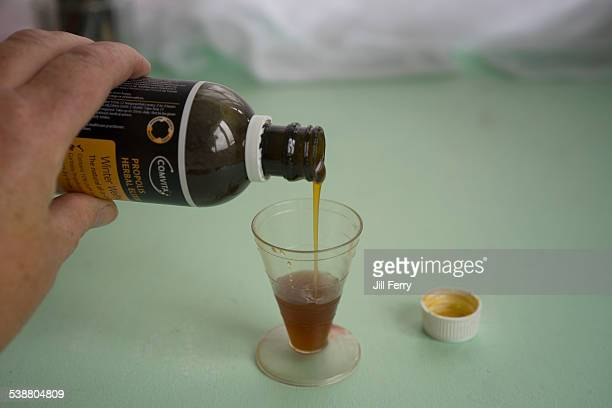Propolis Manuka honey and echinacea herbal elixir which helps relieve cold symptoms being poured into a measuring cup