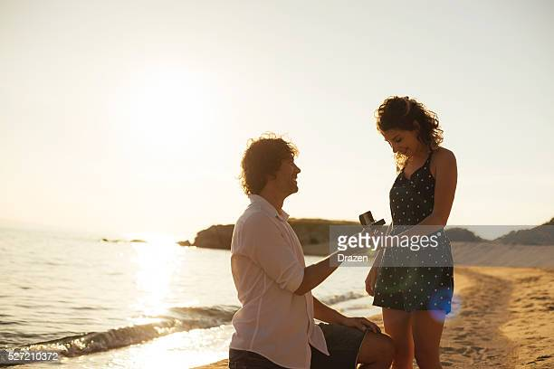Proposing woman at seaside in summer is romantic