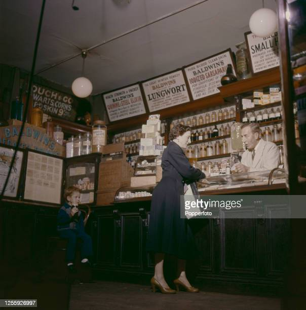 Proprietor Henry Dagnell serves a female customer at Baldwin's herbal store on the Walworth Road in south London in December 1957. A young boy sits...