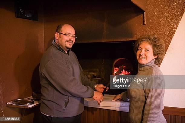 proprietors of casa de pasto justiniano restaurant grill cooking espetada beef skewer. - casa stock pictures, royalty-free photos & images