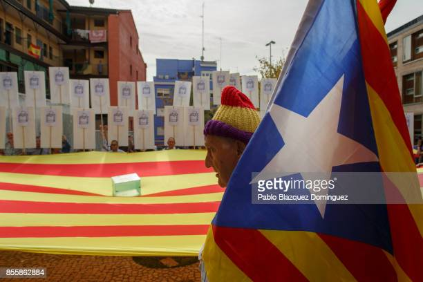 A proreferendum demonstrator holds an independence Catalan flag 'Estelada' next to big Catalan flag with a ballot box laying on top during a protest...