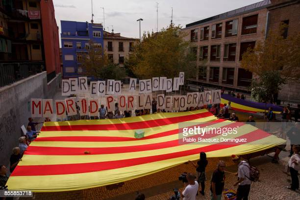 Proreferendum demonstrators display a Catalan flag and a Spanish republican flag as they hold placards reading 'Right to decide Madrid for democracy'...