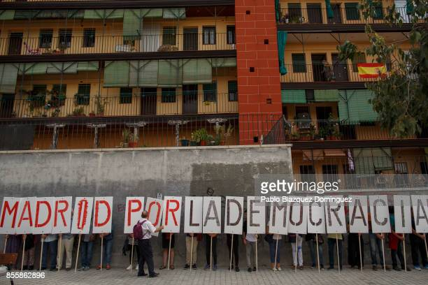 Proreferendum demonstrators hold placards reading 'Madrid for democracy' during a protest in support of Catalan's referendum vote ahead of Sunday's...