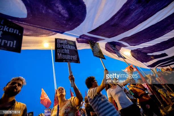 Prorefugee and promigration protesters hold a giant banner as several thousands of people attend a protest at Reichsbrucke bridge in Vienna Austria...
