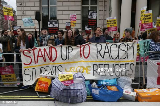 Prorefugee protesters hold placards and a banner as they gather to protest outside the French Embassy in central London on June 18 2016 after most of...