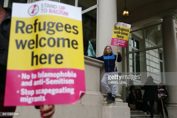 Prorefugee protesters hold placards as they gather to protest outside the French Embassy in central London on June 18 2016 after most of an aid...